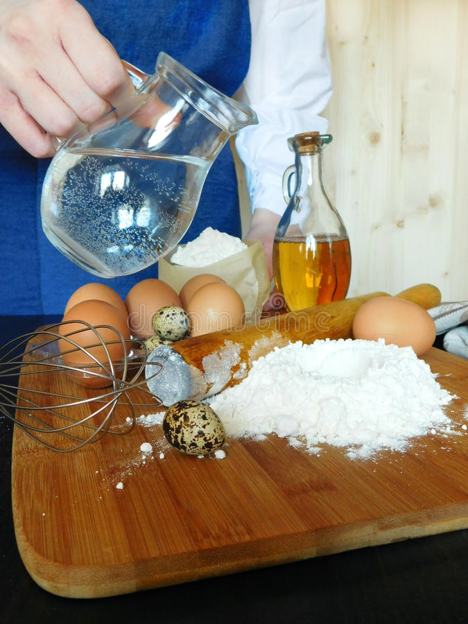 Ingredients for dough kneading. A baker is standing in the background stock photography