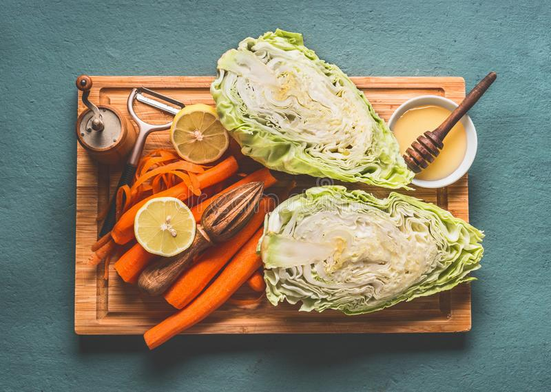 Ingredients for fresh carrot cabbage salad with oil honey dressing in bowl on kitchen table background, top view, with copy space. Vegetarian, low-calorie royalty free stock photos