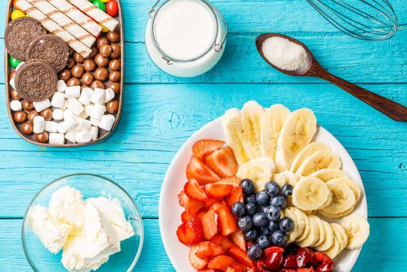 Ingredients for fruit milkshakes. On blue table stock photo