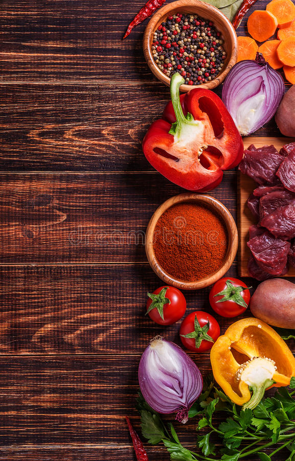 Ingredients for goulash or stew cooking: raw meat,herbs,spices,vegetables on dark wooden background. royalty free stock photography