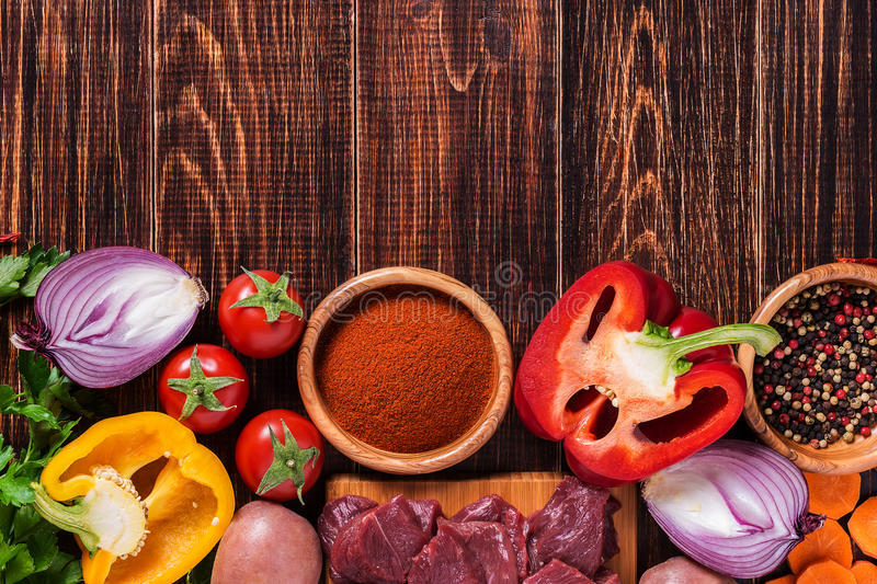 Ingredients for goulash or stew cooking: raw meat,herbs,spices,vegetables on dark wooden background. royalty free stock photo