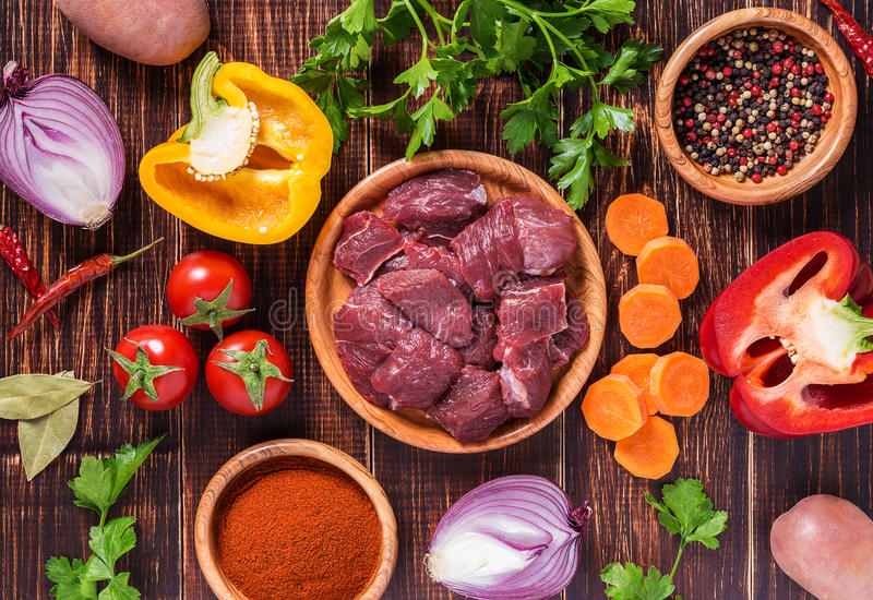 Ingredients for goulash or stew cooking: raw meat,herbs,spices,vegetables on dark wooden background. stock photo