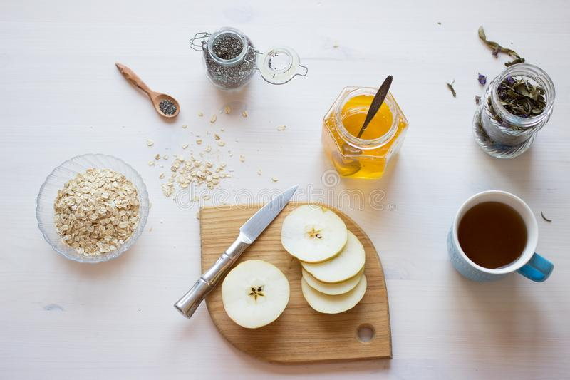 Ingredients for healthy breakfast. Chia seeds, oatmeal cereals and apple on white table. Flatlay royalty free stock photo