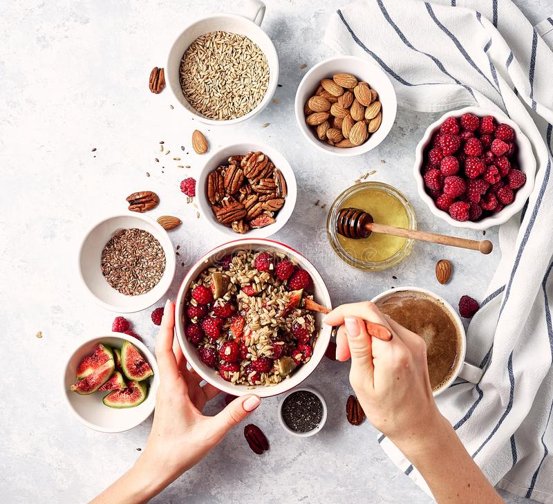 Ingredients for a healthy breakfast, oatmeal with raspberries, figs, pecans, almonds, flax seeds, chia seeds with honey and coffee royalty free stock images