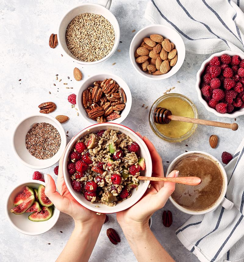 Ingredients for a healthy breakfast, oatmeal with raspberries, figs, pecans, almonds, flax seeds, chia seeds with honey and coffee royalty free stock photos