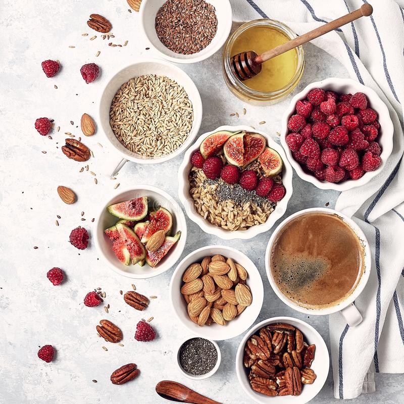 Ingredients for a healthy breakfast, oatmeal with raspberries, figs, pecans, almonds, flax seeds, chia seeds with honey and coffee stock photos