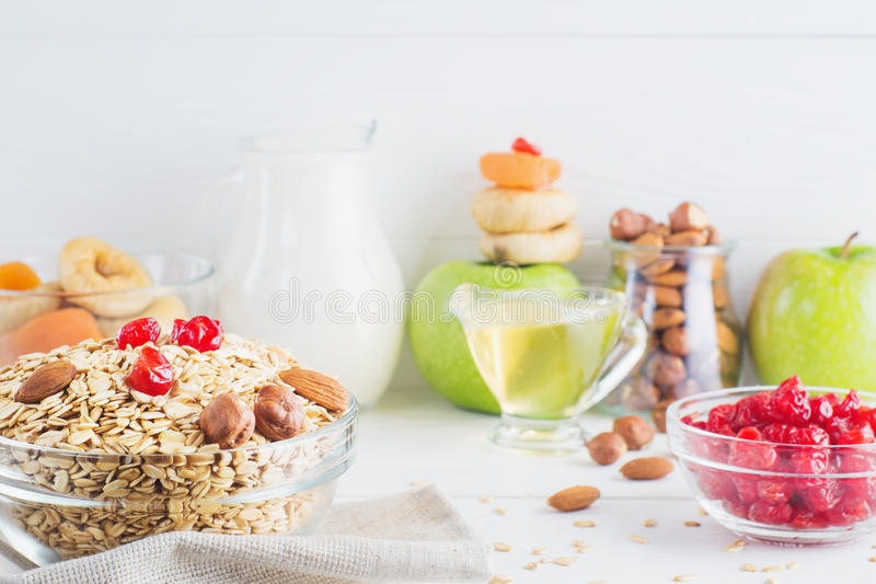 Ingredients for healthy breakfast. Ingredients for healthy breakfast on white wooden background, copy space. Oatmeal, fresh and dried fruit, nuts, honey and stock photo