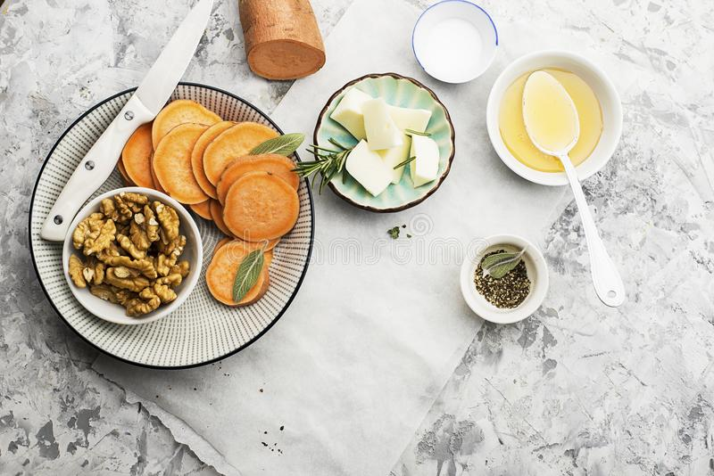 Ingredients for a healthy and comfortable diet: slices of fresh raw sweet potato, honey, walnuts, rosemary cheese, sage stock images