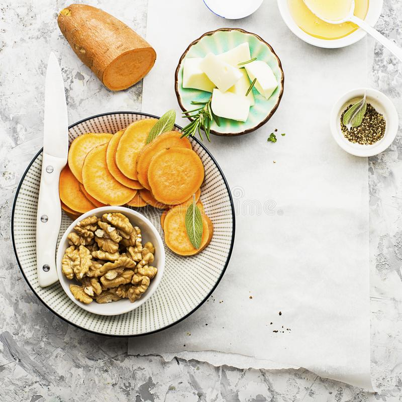 Ingredients for a healthy and comfortable diet: slices of fresh raw sweet potato, honey, walnuts, rosemary cheese, sage stock image