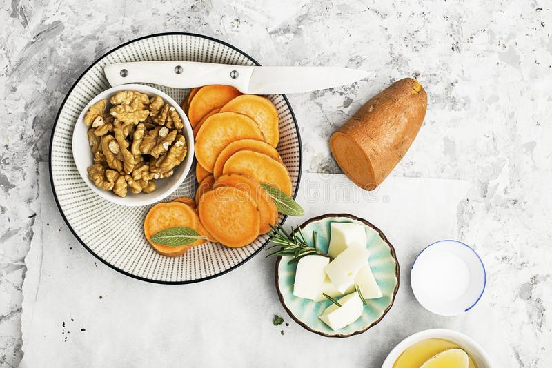 Ingredients for a healthy and comfortable diet: slices of fresh raw sweet potato, honey, walnuts, rosemary cheese, sage royalty free stock image