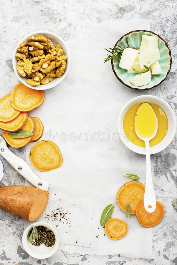 Ingredients for a healthy and comfortable diet: slices of fresh raw sweet potato, honey, walnuts, rosemary cheese, sage stock photos