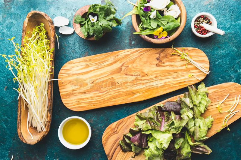 Ingredients for healthy salad - lettuce, sprouts, edibles flowers and arugula. Flat lay, copy space food. Detox. Organic. Nutrition. Salad leaves with herbs and stock photo