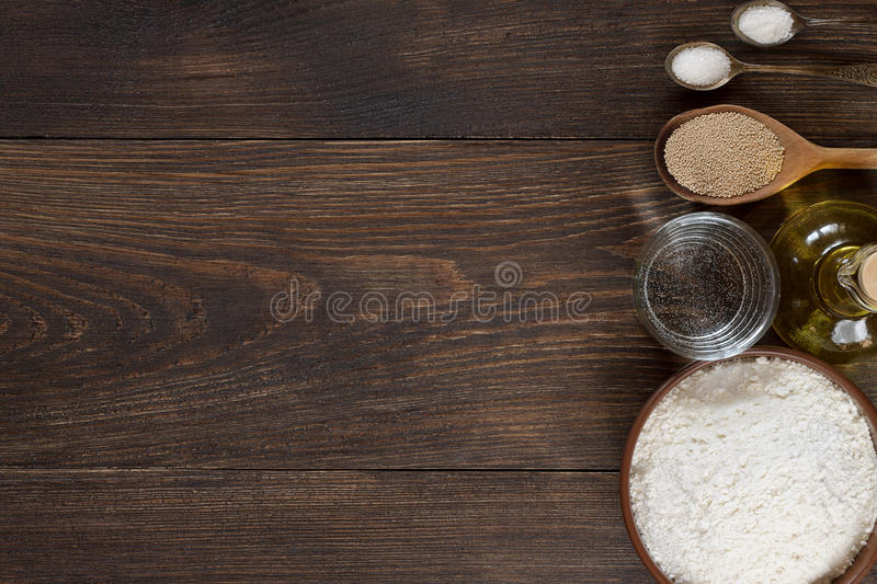 Ingredients for homemade pizza dough on wooden background. royalty free stock image