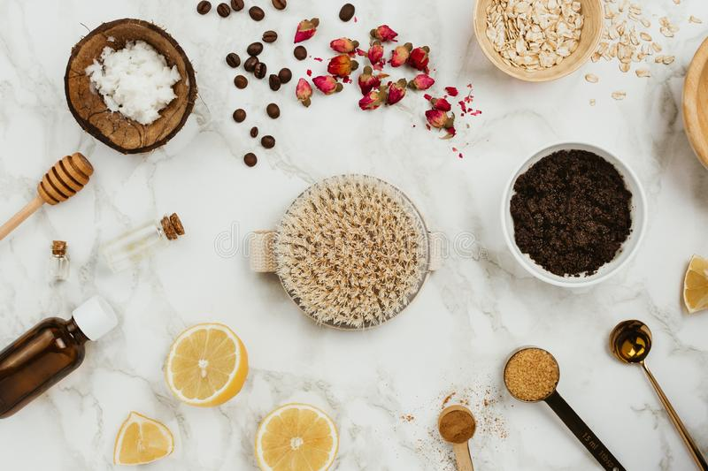 Ingredients for homemade skin scrub on marble: ground coffee, coconut and essential oil, oats, brown sugar, lemons and body brush. Handmade cosmetics concept royalty free stock photos