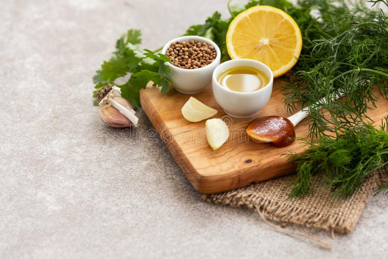 Ingredients for homemade sweet and sour sauce with lemon, honey and herbs on the wooden background. stock photography