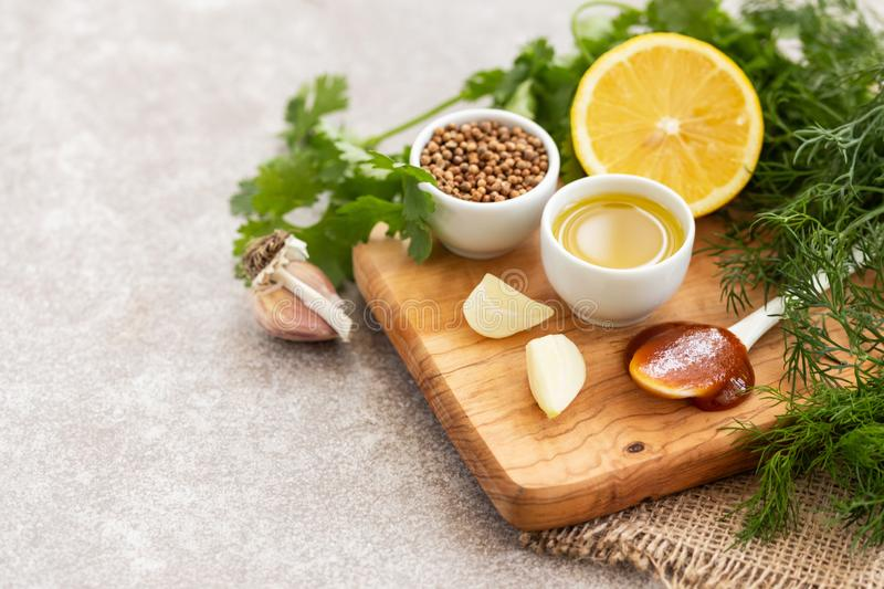 Ingredients for homemade sweet and sour sauce with lemon, honey and herbs on the wooden background. royalty free stock photography