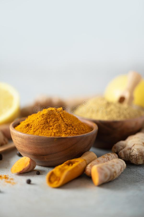 Ingredients for hot ayurvedic drink. Turmeric powder, curcuma root, cinnamon, ginger, lemon over grey background. Copy stock photography