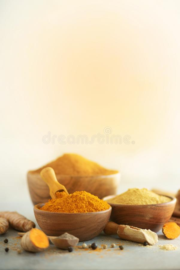 Ingredients for hot ayurvedic drink. Turmeric powder, curcuma root, cinnamon, ginger, lemon over grey background. Copy royalty free stock photos