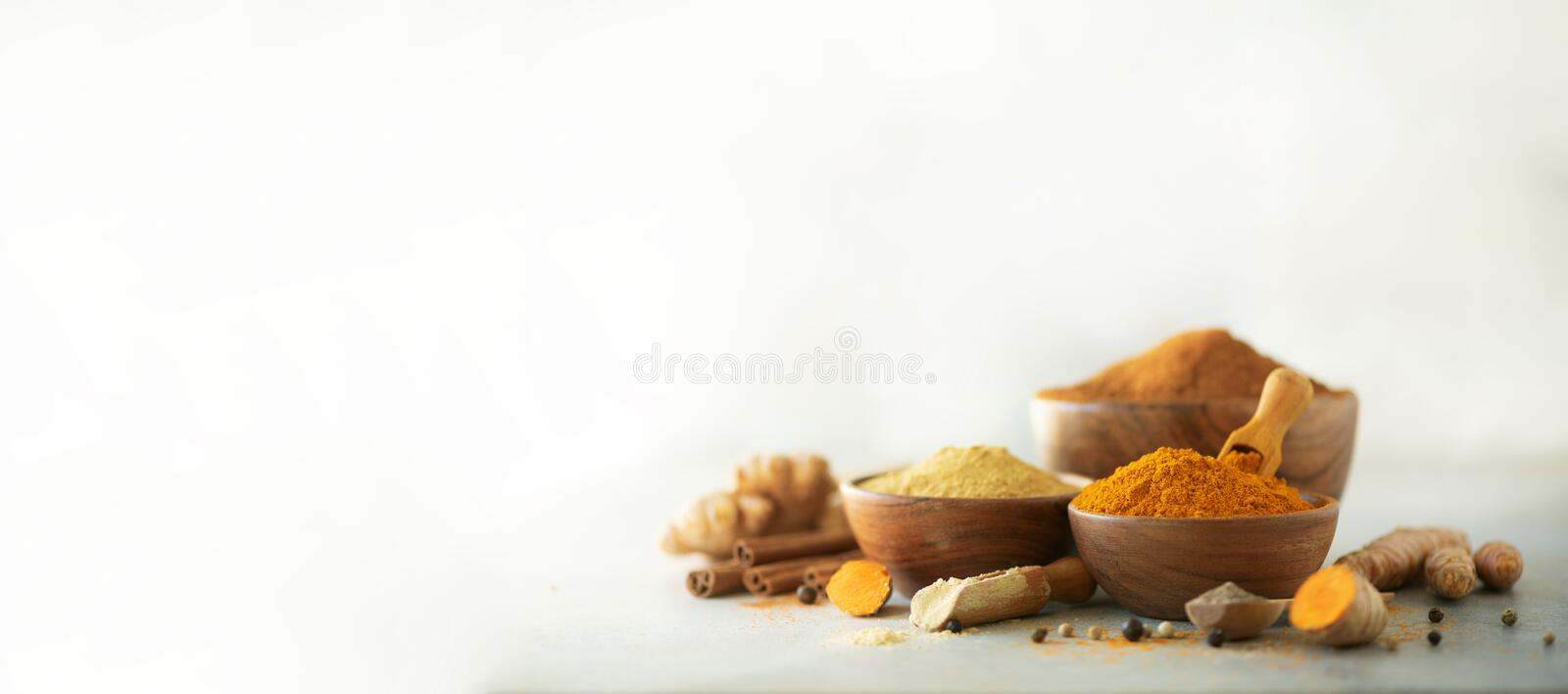 Ingredients for hot ayurvedic drink. Turmeric powder, curcuma root, cinnamon, ginger, lemon over grey background. Copy space, royalty free stock photos
