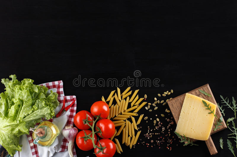 Ingredients for Italian dish. Parmesan cheese, pasta and fresh vegetables. On an old black wooden background. royalty free stock photos