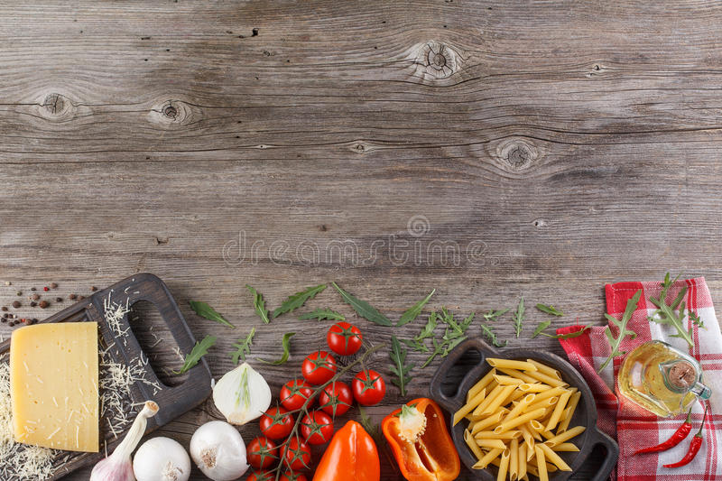 Ingredients for Italian dish. Parmesan cheese, pasta and fresh vegetables. On an old wooden background. stock photos