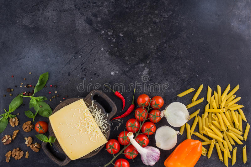 Ingredients for Italian dish. Parmesan cheese, pasta and fresh vegetables. On an old wooden background. royalty free stock images