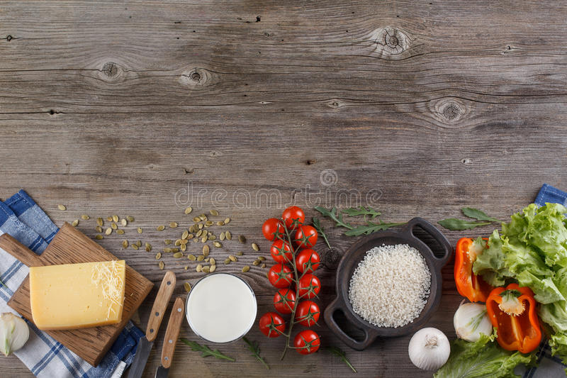 Ingredients for Italian dish. Parmesan cheese, rice and fresh vegetables. On an old wooden background. royalty free stock images