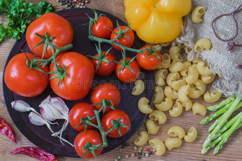 Ingredients for italian food - uncooked Italian pasta and vegetables, different varieties of tomatoes, garlic, asparagus stock photos
