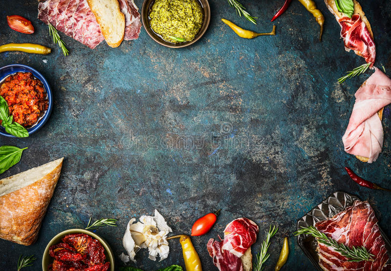 Ingredients for italian snack, bruschetta, crostini or sandwich bar with italian ham, sausage and antipasto on rustic wooden back. Ground, top view, frame stock photography