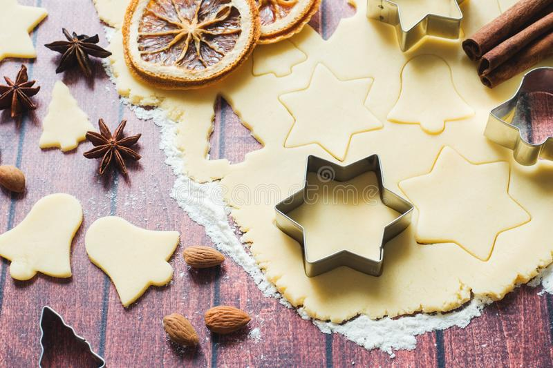 Ingredients for making Christmas cookies. Rolling pin cookie cutters cinnamon flour eggs butter dough on light background with royalty free stock images