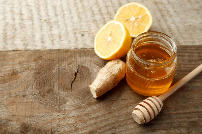 Ingredients for herbal medicine lemon, ginger, honey. Natural products to support the immune system in winter, vintage wooden back royalty free stock photo