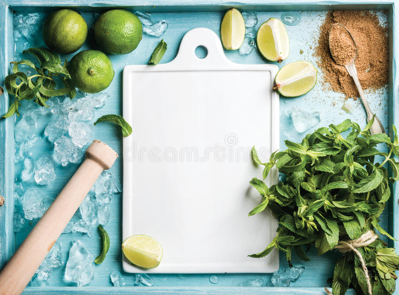 Ingredients for making mojito summer cocktail: chipped ice, mint leaves, brown sugar and lime on turquoise blue painted stock image
