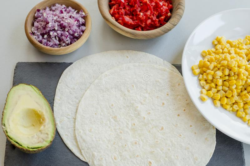 Ingredients for Mexican vegetarian tacos in bowls on light table stock image