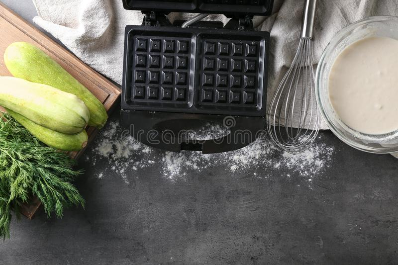 Ingredients and modern maker for preparing of squash waffles on grey table stock photos