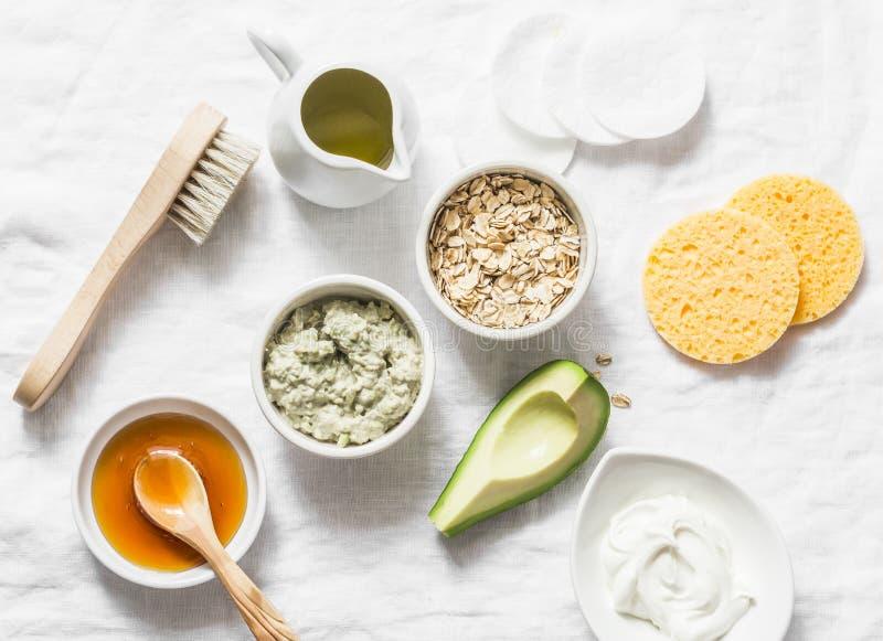 Ingredients for moisturizing, nourishing, anti-aging wrinkle face mask - avocado, olive oil, oatmeal, natural yogurt on light back stock photos