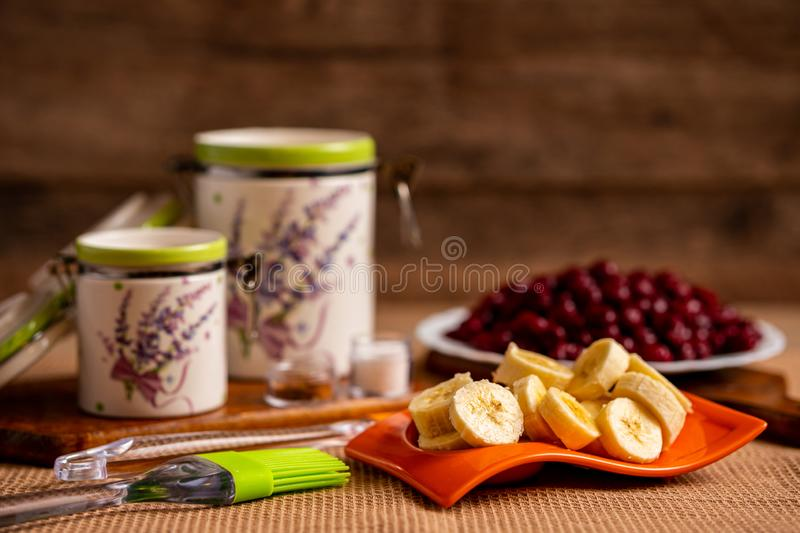 Ingredients needed for making banana and cherry muffin. Ingredients needed for making banana-cherry muffin. Blurry view of container jars and sour cherries at royalty free stock photo