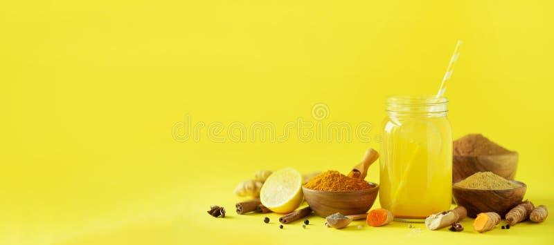 Ingredients for orange turmeric drink on yellow background. Lemon water with ginger, curcuma, black pepper. Vegan hot drink stock image