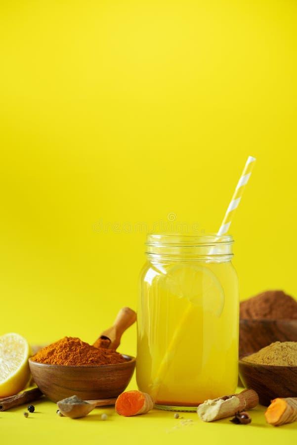 Ingredients for orange turmeric drink on yellow background. Lemon water with ginger, curcuma, black pepper. Vegan hot drink royalty free stock photo