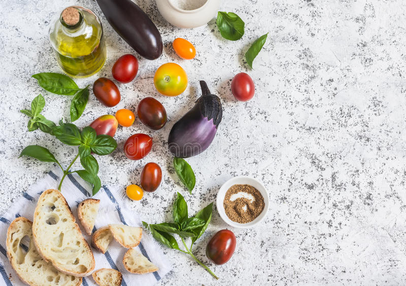 Ingredients for the panzanella salad - eggplant, tomatoes, ciabatta bread, olive oil, and basil. On a light background royalty free stock photography