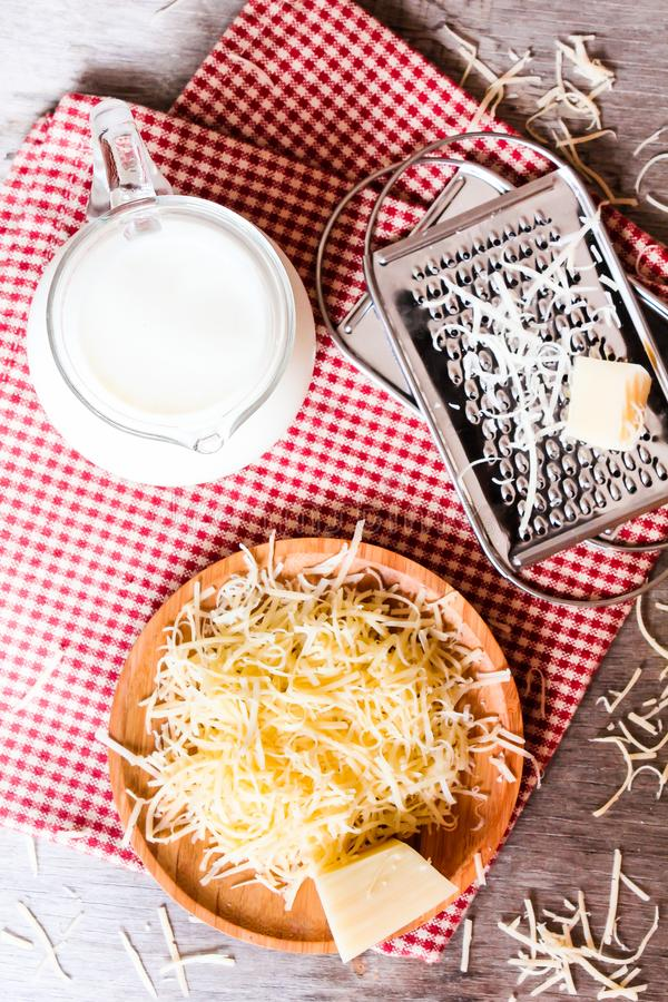 Ingredients for pasta dish or pizza - milk, freshly grated parmesan cheese on a wooden table, and kitchen utensils grater on a w royalty free stock image