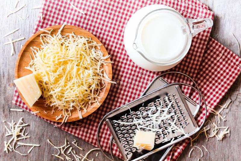 Ingredients for pasta dish or pizza - milk, freshly grated parmesan cheese on a wooden table, and kitchen utensils grater on a w royalty free stock photography