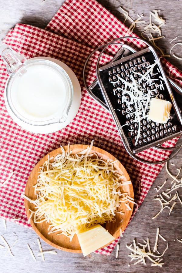 Ingredients for pasta dish or pizza - milk, freshly grated parmesan cheese on a wooden table, and kitchen utensils grater on a w stock photo