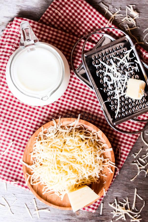 Ingredients for pasta dish or pizza - milk, freshly grated parmesan cheese on a wooden table, and kitchen utensils grater on a w stock photography