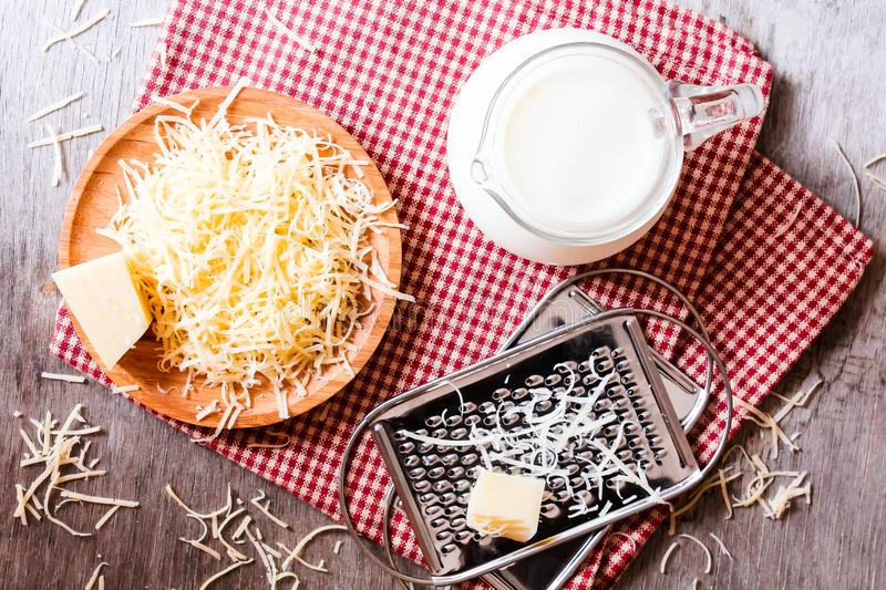 Ingredients for pasta dish or pizza - milk, freshly grated parmesan cheese on a wooden table, and kitchen utensils grater on a w stock image