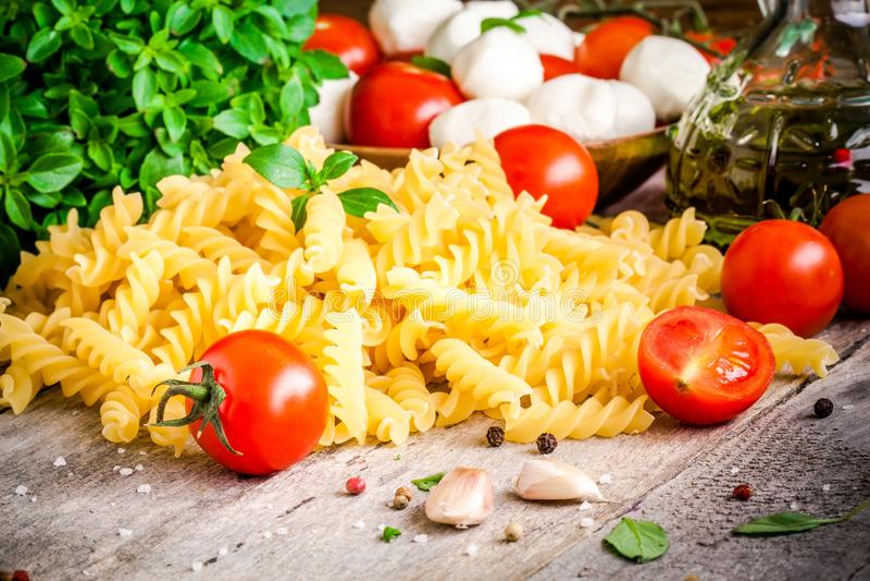 Ingredients for pasta: organic cherry tomatoes, mozzarella, fresh basil, fusilli, garlic and olive oil stock photos