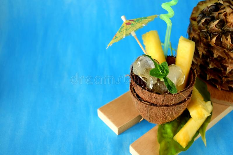Ingredients for pina colada cocktail. Ice cubes and pineapple pieces served in a coconut half decorated with an umbrella stock images