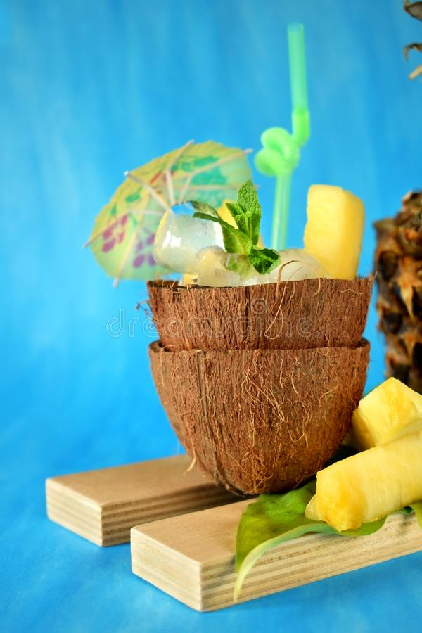 Ice cubes and pineapple pieces served in a coconut half decorated with an umbrella and straw on blue background royalty free stock images