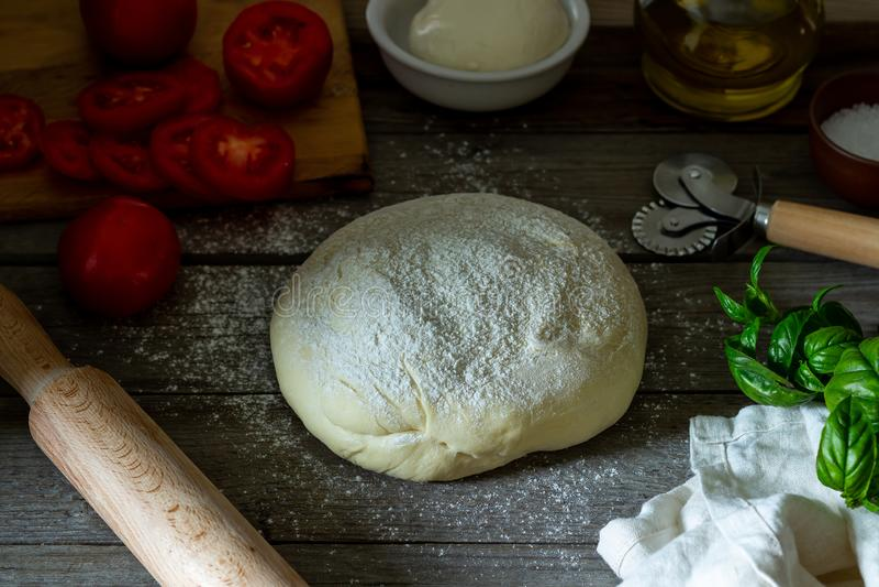 Ingredients for pizza. Dough, tomatoes, mozzarella, basil. Italian cuisine stock image