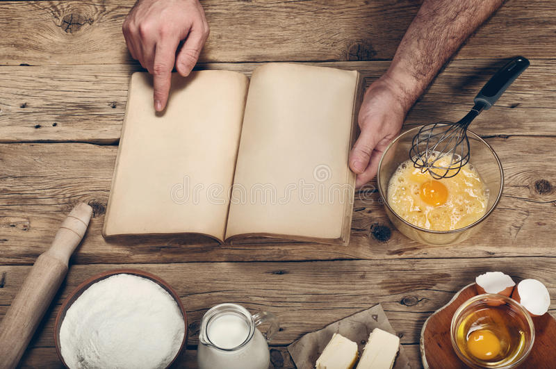 Ingredients for the preparation of bakery products. Man reading a cookbook. Ingredients for the preparation of bakery products. Top view stock photos