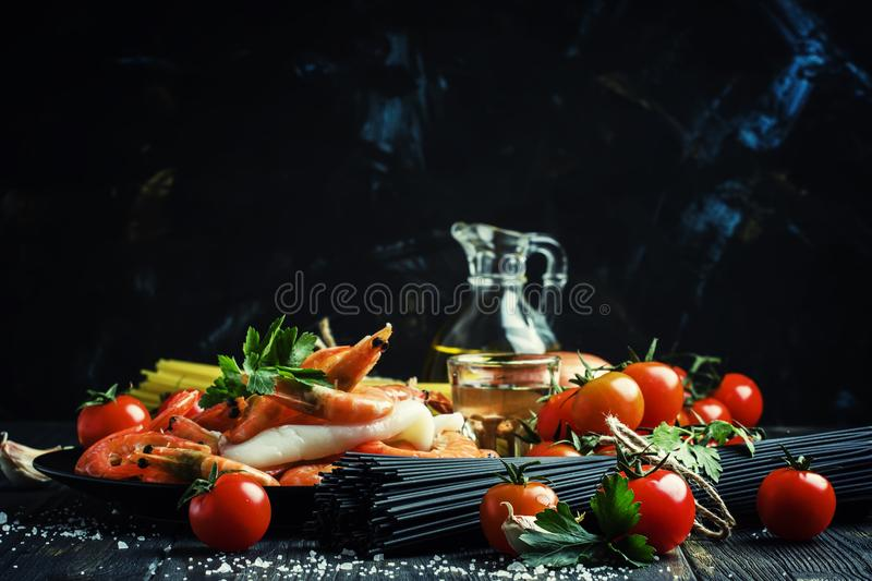 Ingredients for the preparation black pasta with seafood, tomato stock photo